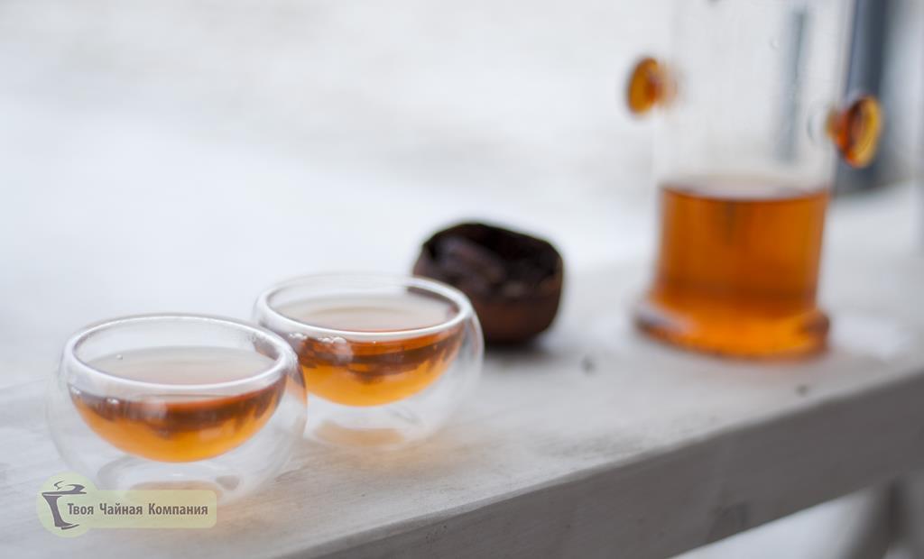 Настой получаемый после заваривания Шу Пуэра в мандарине в стеклянных пиалах с двойными стенками