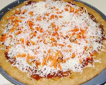 Выложите ингредиенты на тесто и посыпьте моцареллой